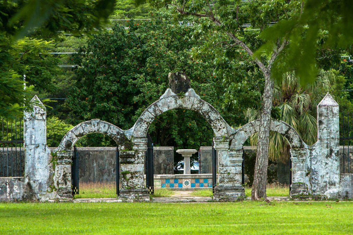 Von der Azotea, der Terrasse am Plaza de España in Guam, sind noch drei steinerne Bögen übriggeblieben, die etwas verloren inmitten der grünen Rasenfläche stehen - © IZO / Shutterstock