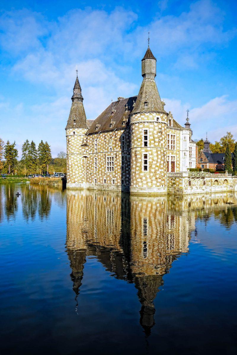 Blick auf das Wasserschloss Jehay mit seiner auffälligen Fassade und dem malerischen Teich, Belgien - © tacna / Fotolia