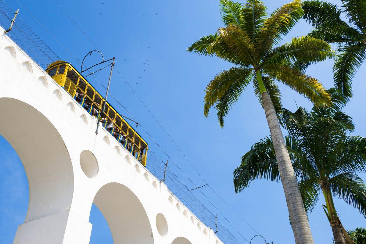 """Die Bögen von Lapa in Rio de Janeiro, Brasilien, sind Teil der Strecke von der Altstadt nach Santa Teresa, auf der die leuchtend gelbe """"Bonde"""" fährt - © lazyllama / Shutterstock"""