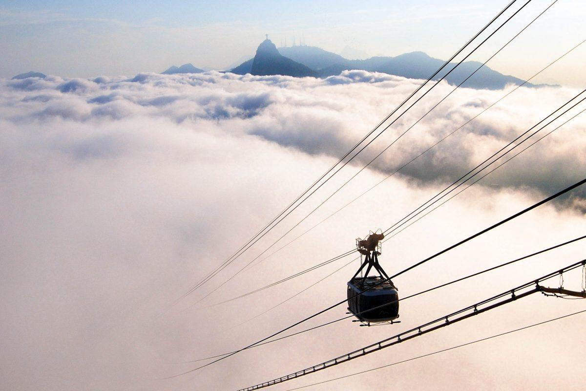 Die Seilbahn auf den Zuckerhut sticht aus den Wolken, die über Rio de Janeiro liegen; im Hintergrund ist die Christusstatue erkennbar, Brasilien - © Publio Furbino / Shutterstock