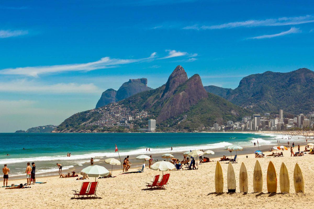 """Surfer und Sonnenanbeter tummeln sich in Rios Stadtteil Ipanema auf der hellen Sandfläche, die durch """"postos"""" in Abschnitte unterteilt ist, Brasilien - © Donatas Dabravolskas / Shutterstock"""