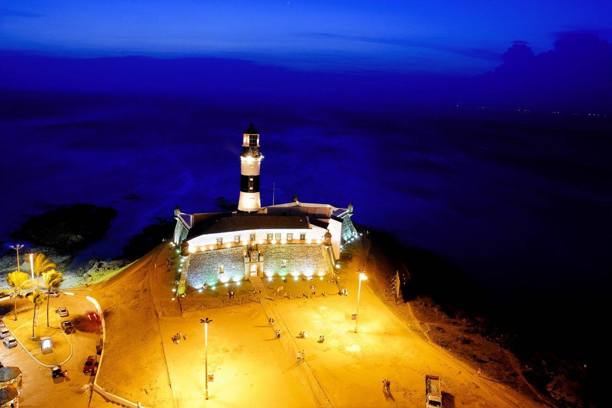 Das Fort und der Leuchtturm Farol da Barra in Salvador da Bahia, Brasilien sind in der Nacht spektakulär beleuchtet - © Vinicius Tupinamba / Shutterstock