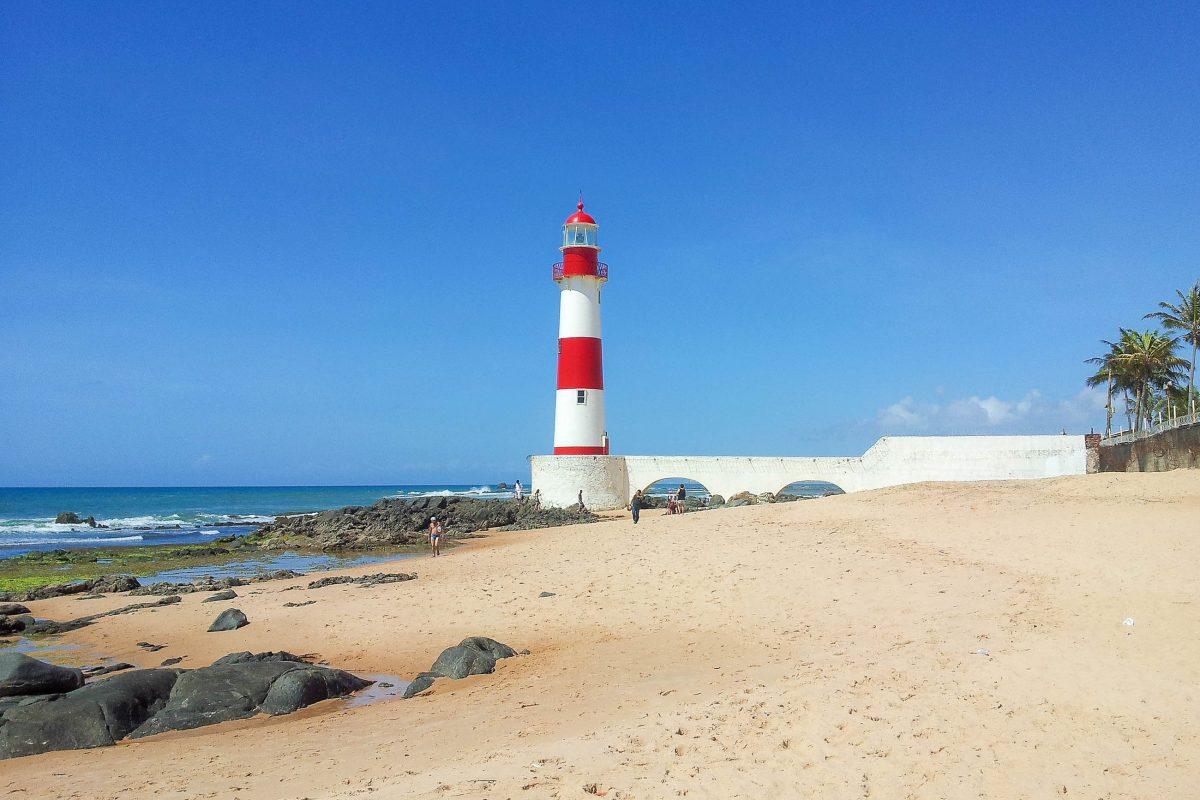 Der rot-weiß gestreifte Farol de Itapuã passt genau ins Bild eines malerischen Strandes und ist ein beliebtes Fotomotiv am Praia da Itapuã, Salvador, Brasilien - © FRASHO / franks-travelbox