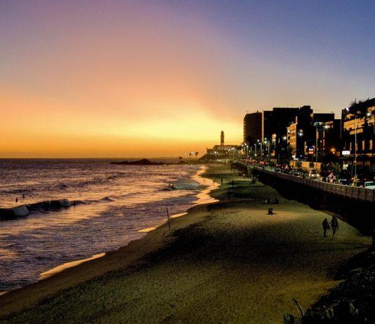 Spektakulärer Sonnenuntergang am Praia da Barra mit dem Farol da Barra als markanten Punkt, Salvador da Bahia, Brasilien - © faberfoto / Shutterstock