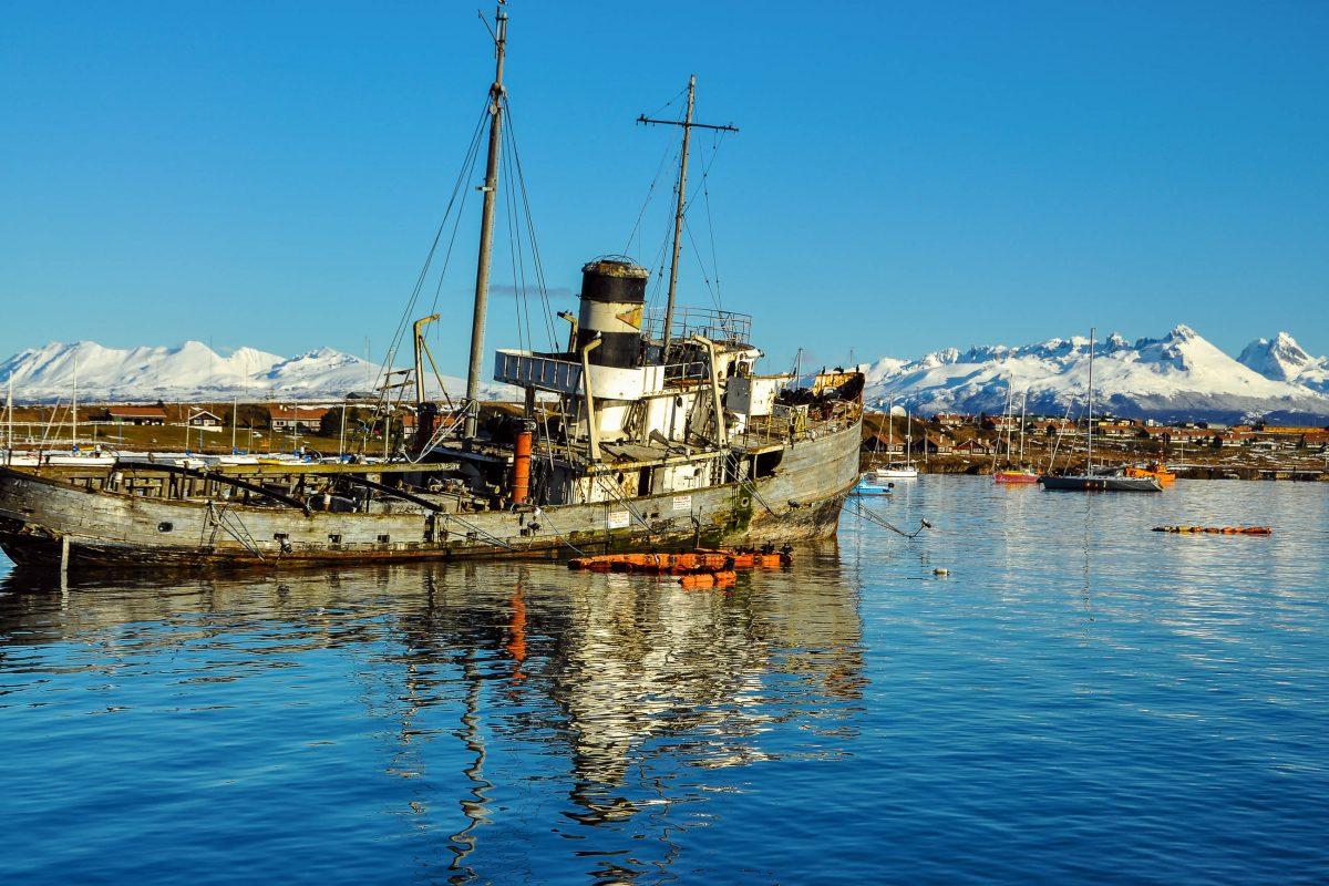 Altes Boot mit den Bergen von Feuerland im Hintergrund, Chile - © Jess Kraft / Shutterstock