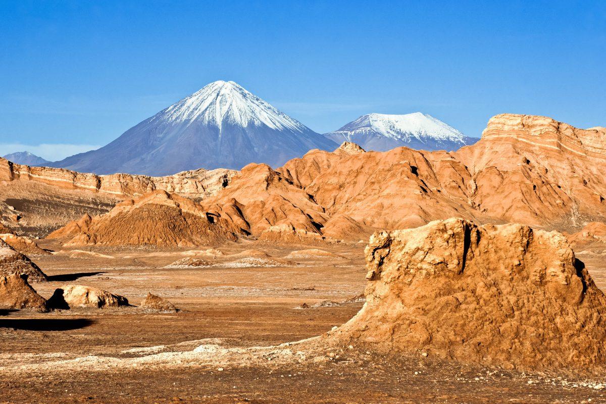 Die schneebedeckten Gipfel der beiden Vulkane Licancabur and Juriques heben sich vor dem Valle de la Luna in der Atacama-Wüste ab, Chile - © Ksenia Ragozina / Shutterstock