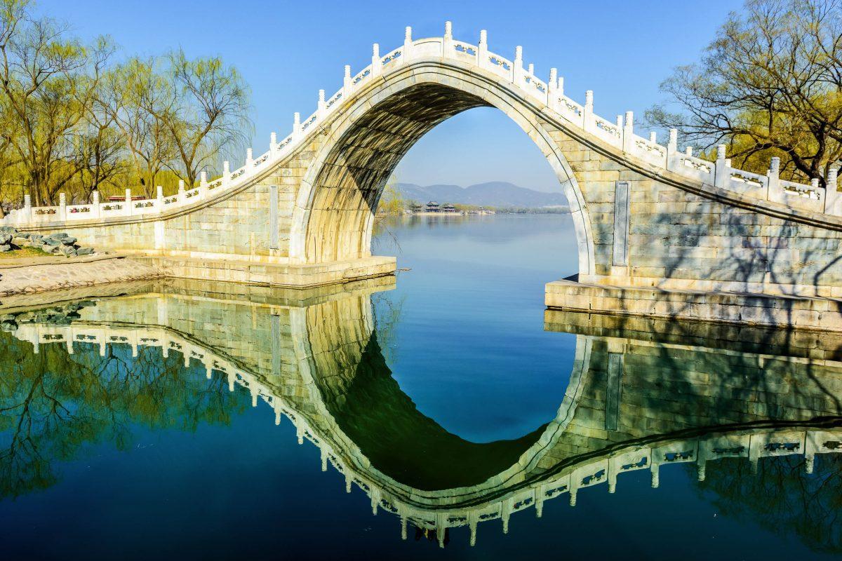 Die kunstvoll geschwungene Jadeband-Brücke im kaiserlichen Sommerpalast im Morgengrauen, Peking, China - © Jixin YU / Shutterstock