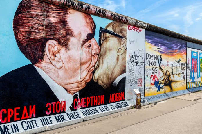 "Der ""Bruderkuss"" zwischen Leonid Breschnew und Erich Honecker gehört zu den berühmtesten Motiven der East Side Gallery in Berlin, Deutschland - © turtix / Shutterstock"