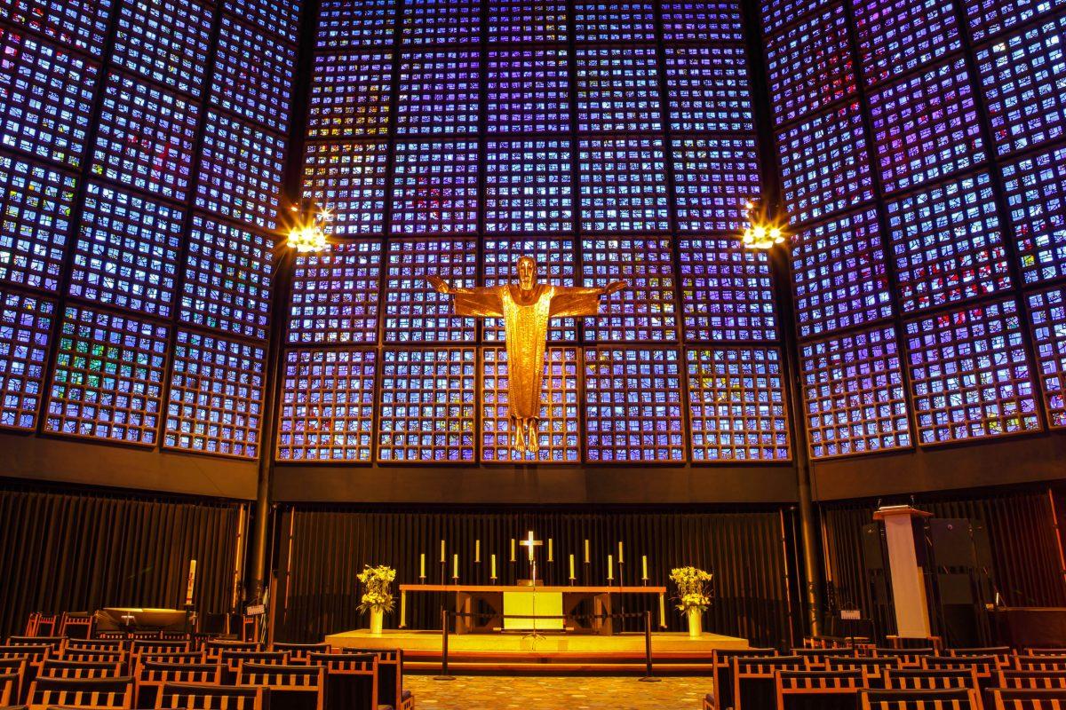 Der Innenraum der evangelischen Kaiser-Wilhelm-Gedächtniskirche in Berlin, Deutschland, wird von 20.000 Glasfenstern in ein faszinierendes blaues Licht getaucht - © Ariy / Shutterstock