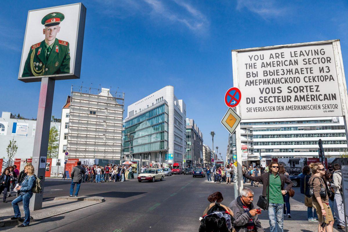Die beiden Hinweistafeln über das Betreten und Verlassen des amerikanischen Sektors am Checkpoint Charlie in Berlin, Deutschland, sind nicht mehr original - © Oscity / Shutterstock