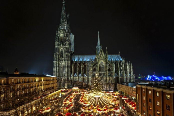 Blick über den abendlichen Weihnachtsmarkt mit seinen etwa 150 schneckenförmig angeordneten und festlich beleuchteten Ständen am Kölner Dom, Deutschland - © Thomas Ramsauer / Shutterstock