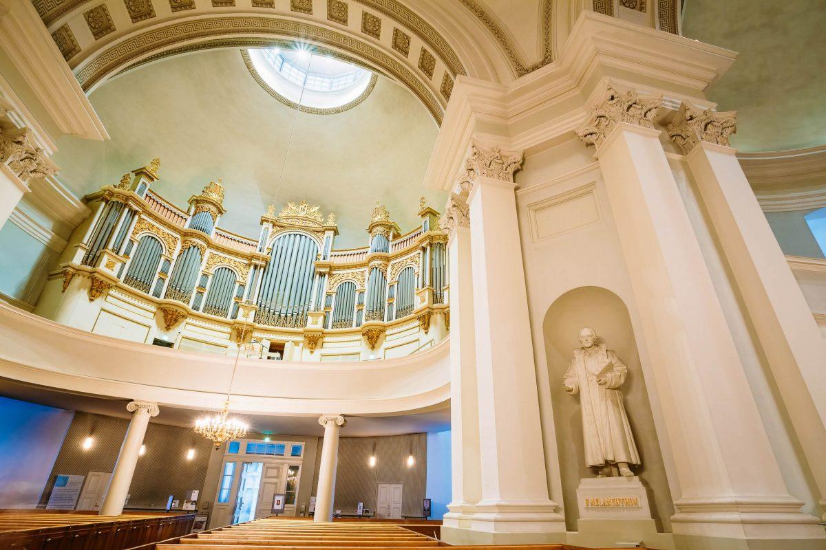 Den schlichten weißen Innenraum des Doms von Helsinki, Finnland, schmücken die Statuen der Reformatoren Martin Luther, Philipp Melanchthon und Mikael Agricola - © Grisha Bruev / Shutterstock