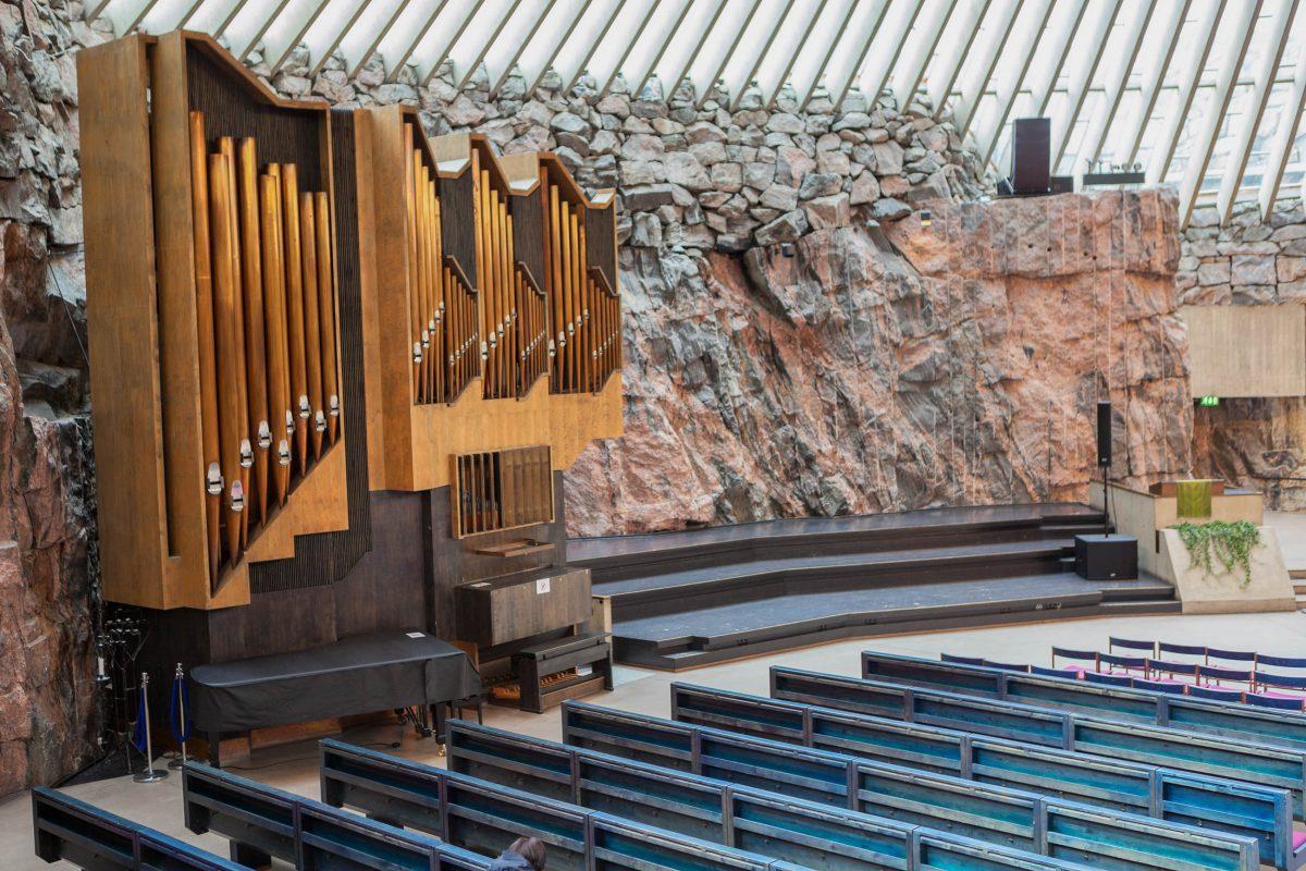 Der steinerne Altar und die hölzerne Orgel an der nackten Felswand der Temppeliaukio Kirche in Helsinki, Finnland, sind nahezu unscheinbar - © Kekyalyaynen / Shutterstock