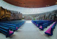 Die Innenwände der Tempelliaukio-Kirche bestehen aus nacktem Stein, das Dach aus poliertem Kupfer und für die Beleuchtung sorgen 180 langgestreckte Fenster, Helsinki, Finnland - © Mikhail Markovskiy / Shutterstock