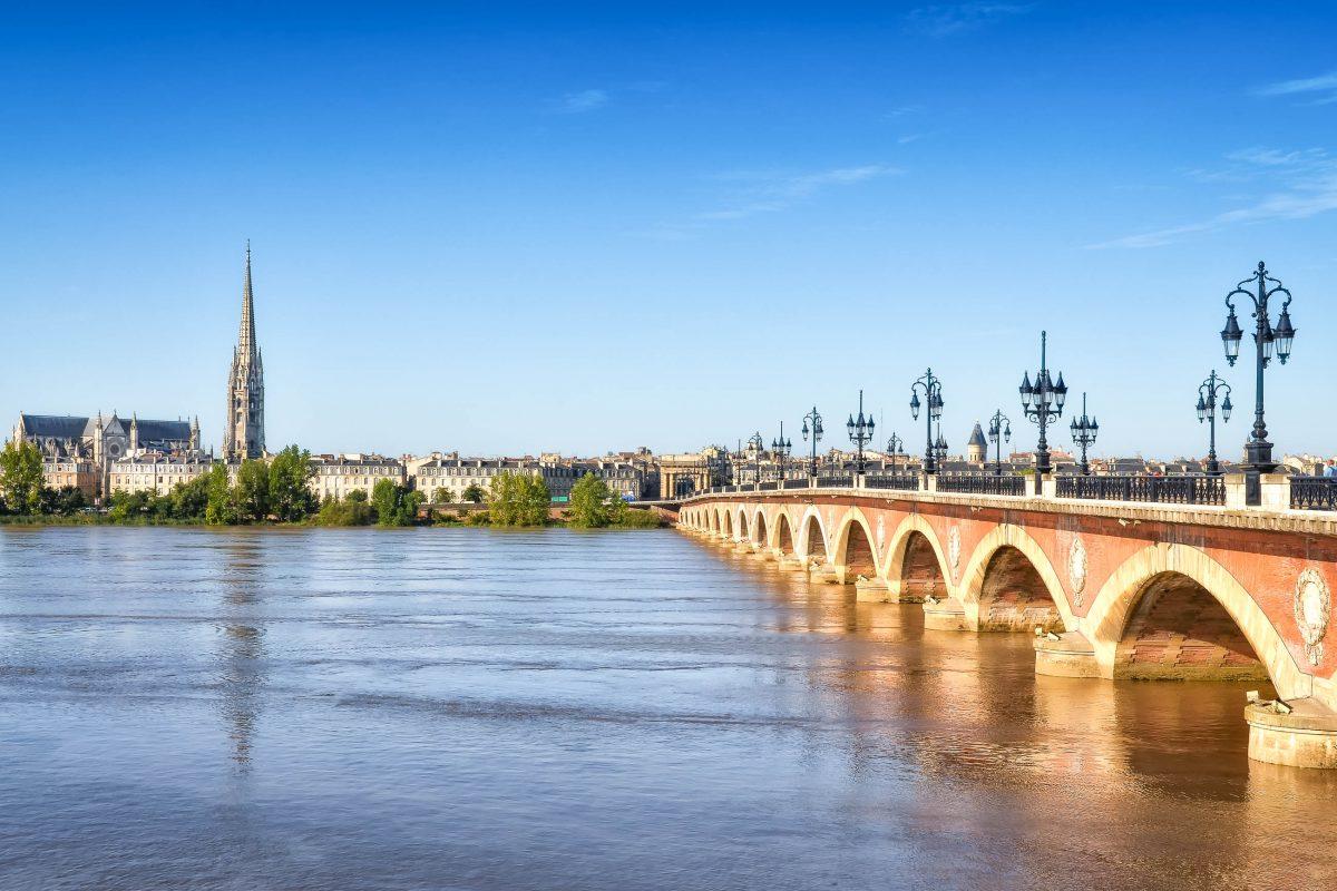 Der Pont de pierre, die erste Brücke der Stadt Bordeaux mit der Basilika Saint Michel im Hintergrund, Frankreich - © Martin M303 / Shutterstock