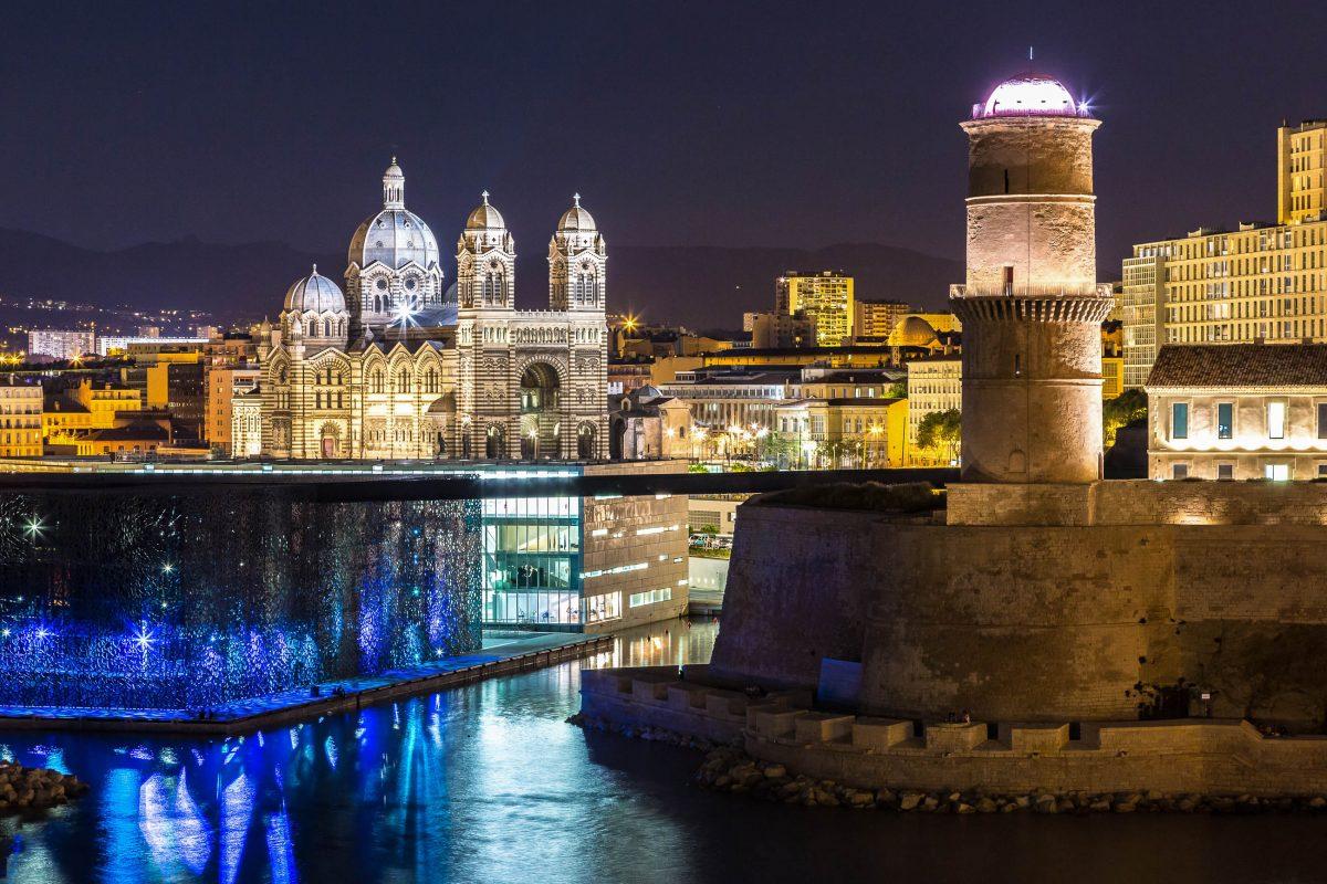 """Der phallusähnliche Signalturm """"Tour de Fanal"""" des Forts Saint-Jean am Eingang zum Vieux Port, im Hintergrund die Kathedrale von Marseille, Frankreich - © S-F / Shutterstock"""