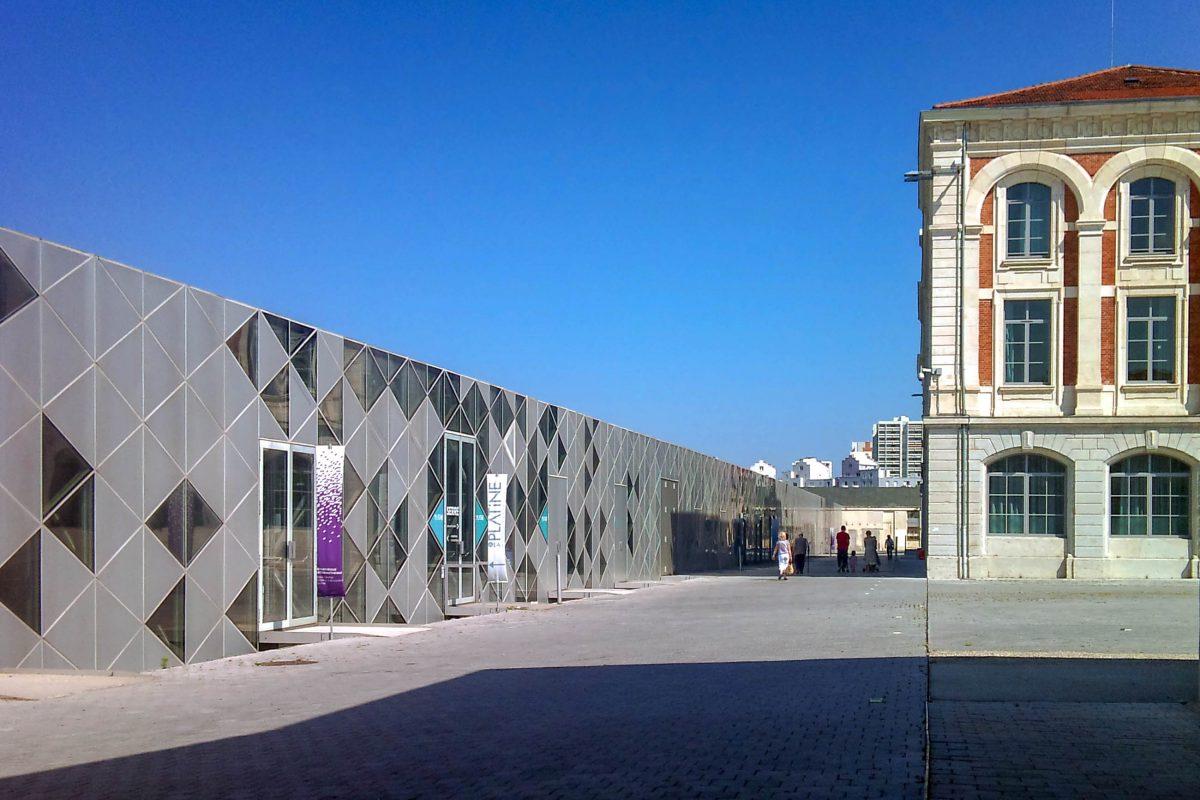 In der Cité du Design in einer ehemaligen Waffenfabrik in Saint-Étienne, Frankreich, trifft moderne Glas-Architektur auf Backsteinbauten des 19. Jahrhunderts - © Touam (Hervé Agnoux) CC BY-SA3.0/Wiki