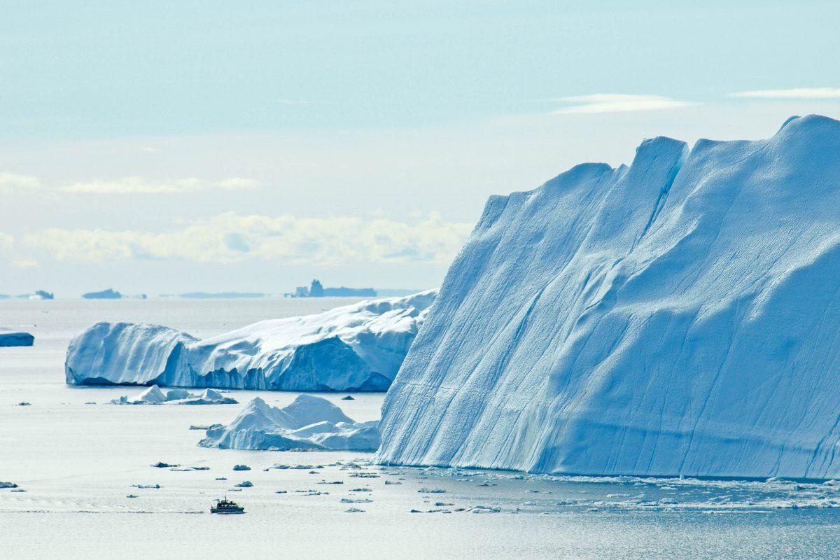 Ein riesiger Eisberg im Ilulissat-Eisfjord an der Westküste Grönlands, man beachte das kleine Boot im Vordergrund - © finecki / Fotolia