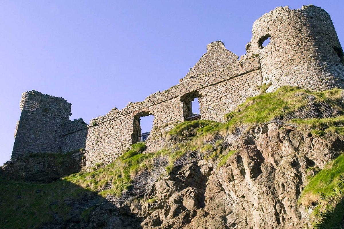 Die Ruinen von Dunluce Castle ragen heute wie abgebrochene Zähne in den grauen Himmel Nordirlands, Großbritannien - © keith robinson / Fotolia