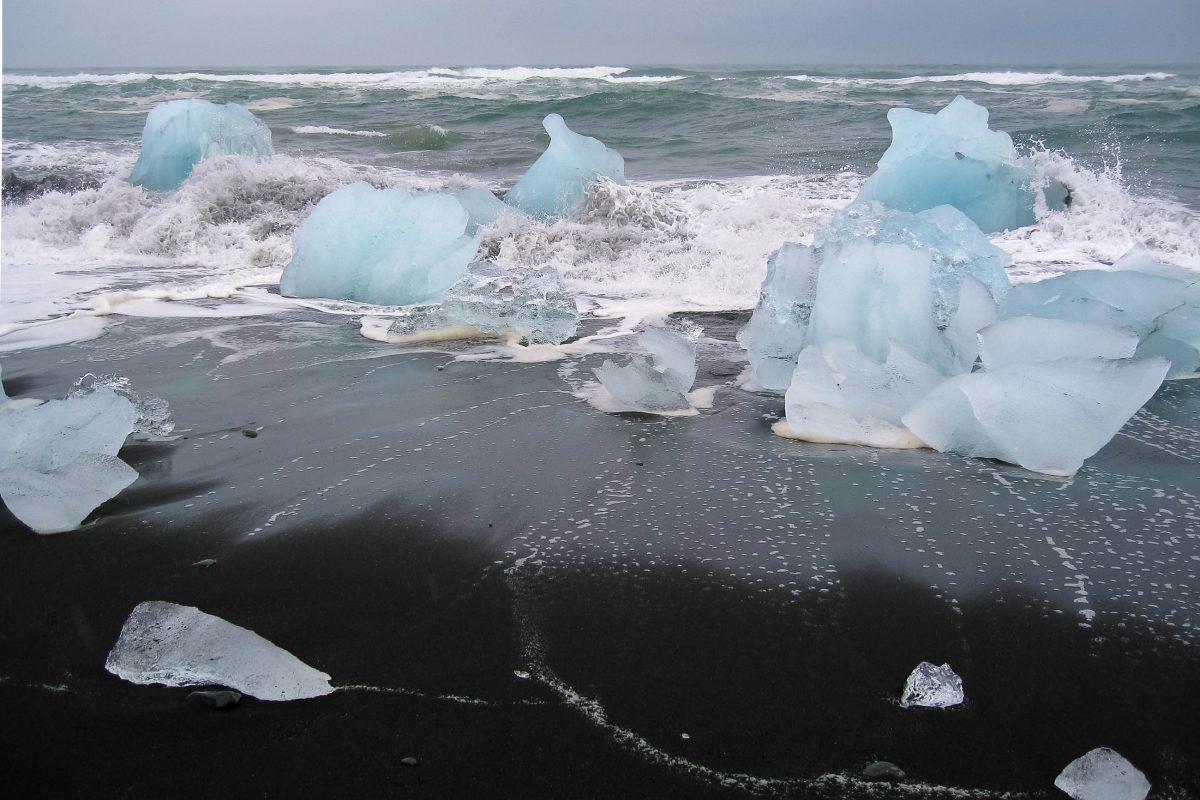 Der pechschwarze Lava-Sandstrand bietet den perfekten Hintergrund für die in allen nur erdenkbaren Blautönen schimmernden Eisstücke des Jökulsárlón, Island - © FRASHO / franks-travelbox