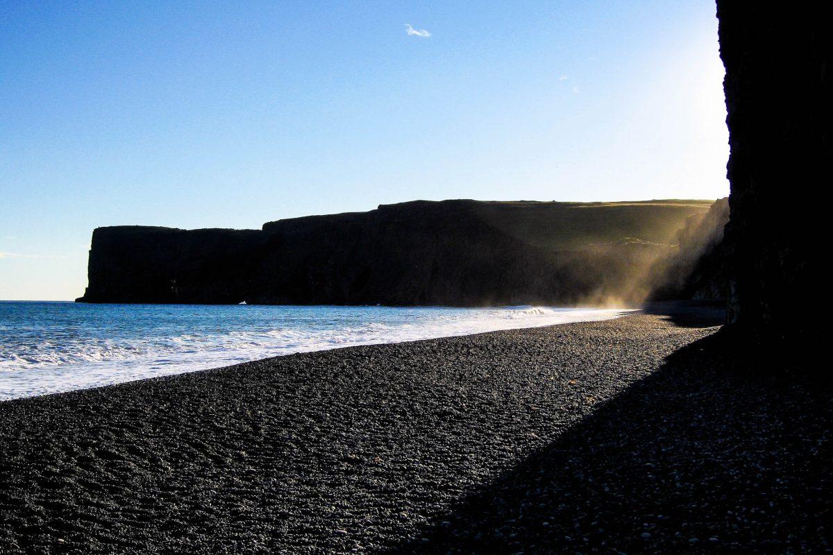 Kurz vor Sonnenuntergang schaffen die pechschwarzen Felsen in der Lagune Dyrhólaós mit dem Blau von Himmel und Meer einmalige Farbenspiele, Island - © FRASHO / franks-travelbox
