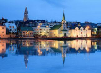 Blick auf die beiden Türme der Kirche Hallgrimskirkja und der lutherischen Freikirche direkt am Tjörnin-See in Reykjavik, Island - © Dennis van de Water / Shutterstock