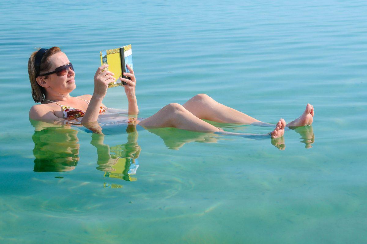 Eine Besucherin liest ein Buch während sie im Toten Meer schwimmt, Israel/Jordanien - © vicspacewalker / Fotolia