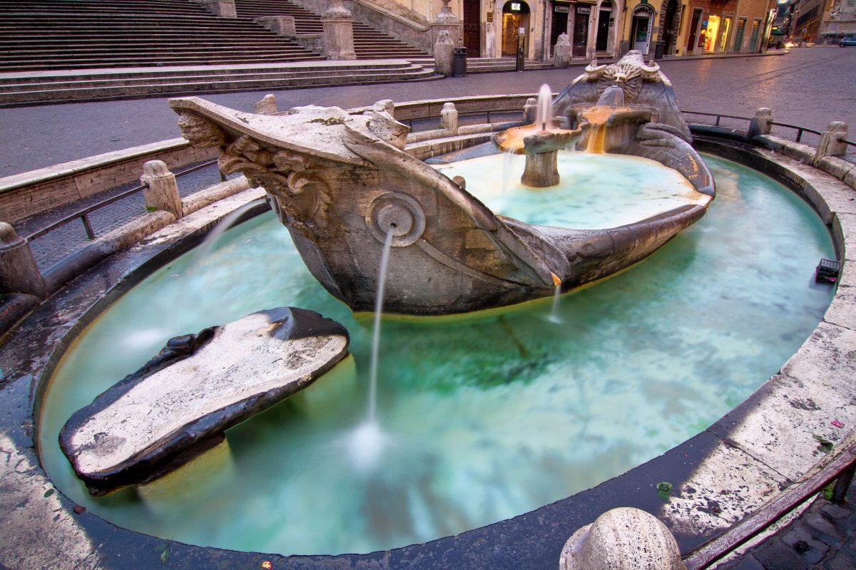 Die Fontana della Barcaccia am Fuß der Spanischen Treppe in Form einer Barkasse soll an die Hochwasserkatastrophe an den Weihnachtstagen des Jahres 1598 in Rom erinnern, Italien - © mdlart / Shutterstock