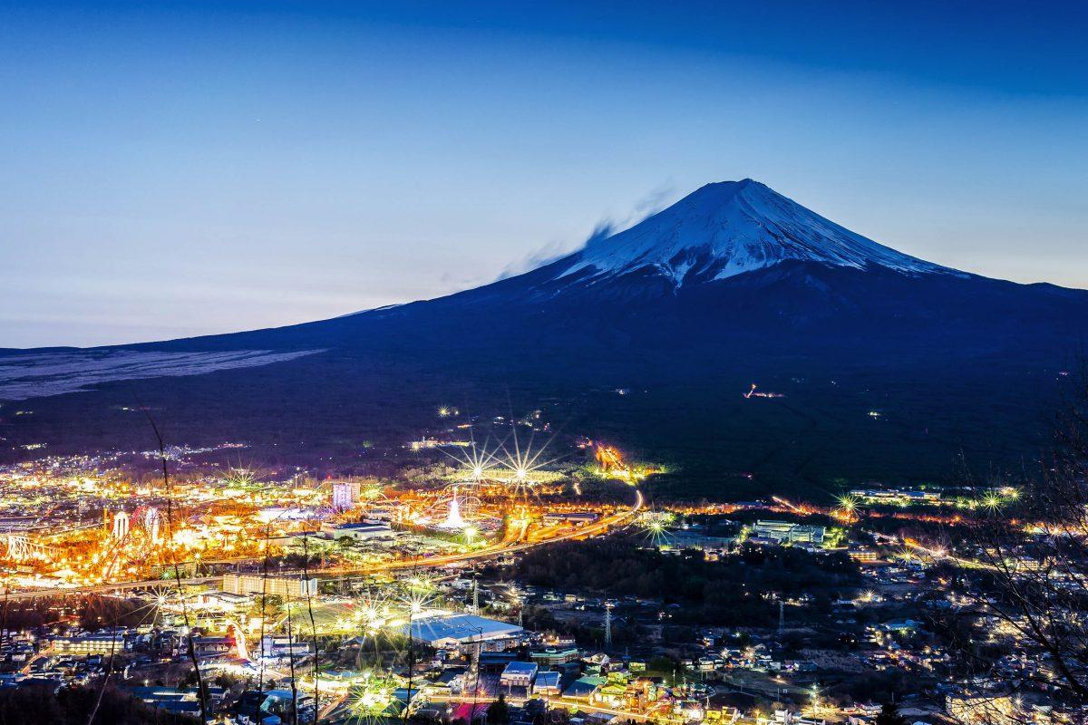 Die hell erleuchtete Stadt Fujiyoshida in der Dämmerung am Fuß des berühmten Mount Fuji in Japan - © skyearth / Shutterstock