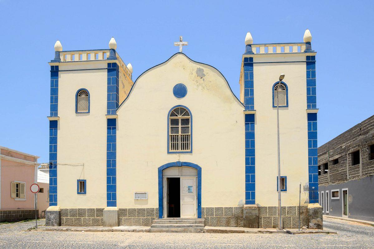 """Blick auf die Kirche """"Igreja da Santa Isabel"""", ein schmuckes, zartgelbes Kolonialstil-Gebäude mit zwei wuchtigen Türmen in Sal Rei, Boa Vista, Kap Verde - © uigsantos / Shutterstock"""