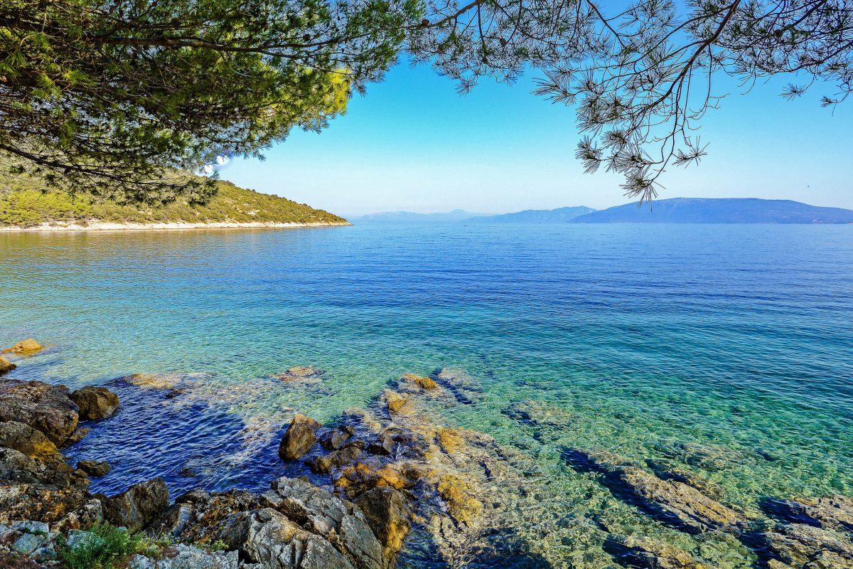 Etwas außerhalb von Valun auf der Insel Cres werden die Kiesstrände von naturbelassenen Felsbänken abgelöst, Kroatien - © ah_fotobox / Shutterstock
