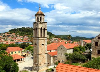 In einem Meer aus roten Ziegeldächern thront auf dem malerischen Hauptplatz von Blato die stolze Allerheiligen-Kirche Svih Svetih, Insel Korcula, Kroatien - © Berni / Shutterstock
