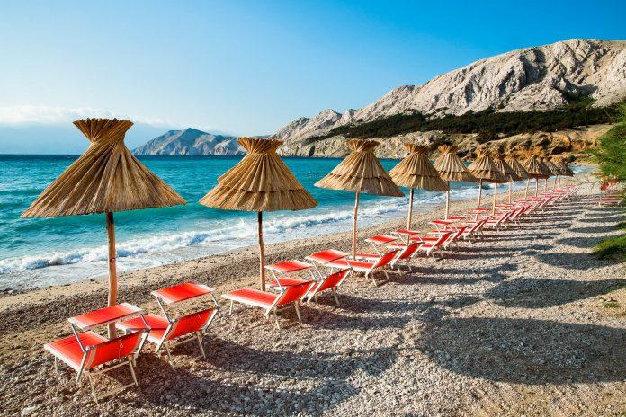 Sonnenliegen am Strand von Baska auf der Insel Krk warten auf die Badegäste, Kroatien - © Pablo Debat / Shutterstock