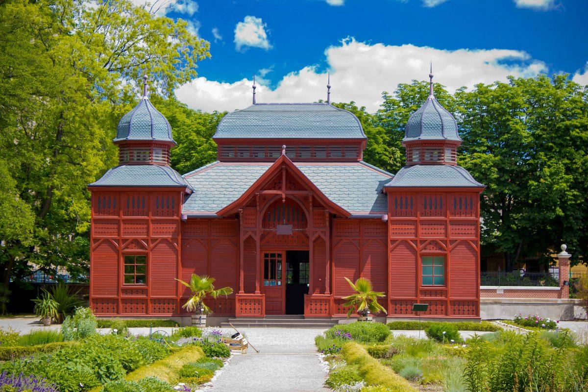 Der tiefrote Pavillon im Botanischen Garten von Zagreb bildet einen attraktiven Kontrast zur grünen Idylle seiner Umgebung, Kroatien - © xbrchx / Shutterstock
