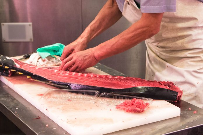 Ein geübter Fischhändler am Fischmarkt in Male braucht etwa 2 Minuten um einen 50cm langen Tunfisch zu filetieren, Malediven - © AQ_taro_neo / Shutterstock