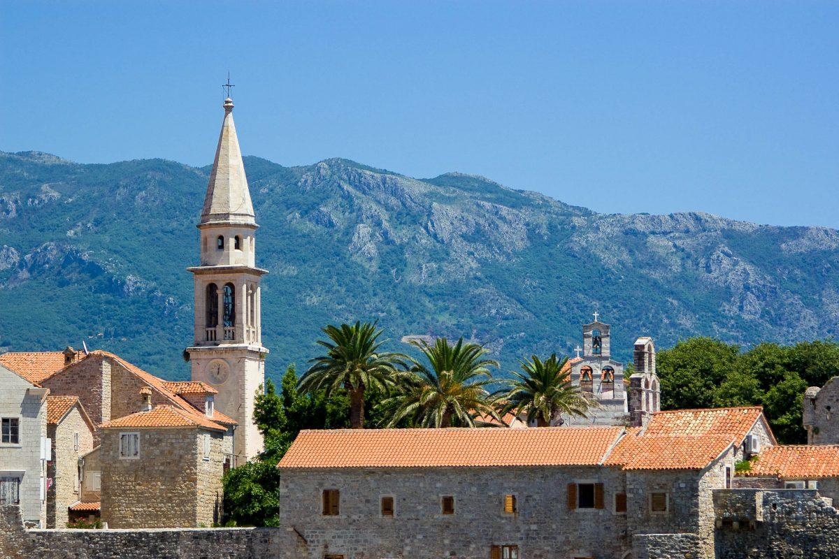 Der Glockenturm der Kirche Sveti Ivan ragt weit über das ziegelrote Dächermeer von Budva im Süden Montenegros - © Andrey Krepkih / Shutterstock