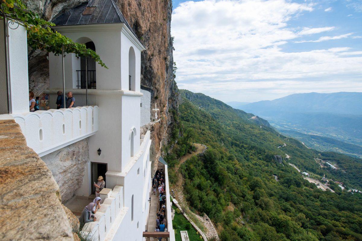Der Panoramablick von der steilen Bergflanke des Felsenklosters Ostrog reicht kilometerweit über die Bjelopavlićko-Ebene in Montenegro - © Pe3k / Shutterstock