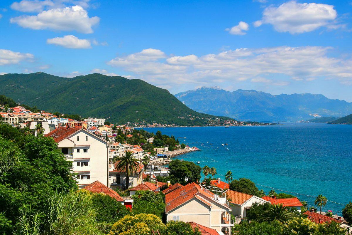 Herceg Novi schmiegt sich malerisch an die dunkelgrünen Hänge der Bucht von Kotor in Montenegro - © Planner / Shutterstock