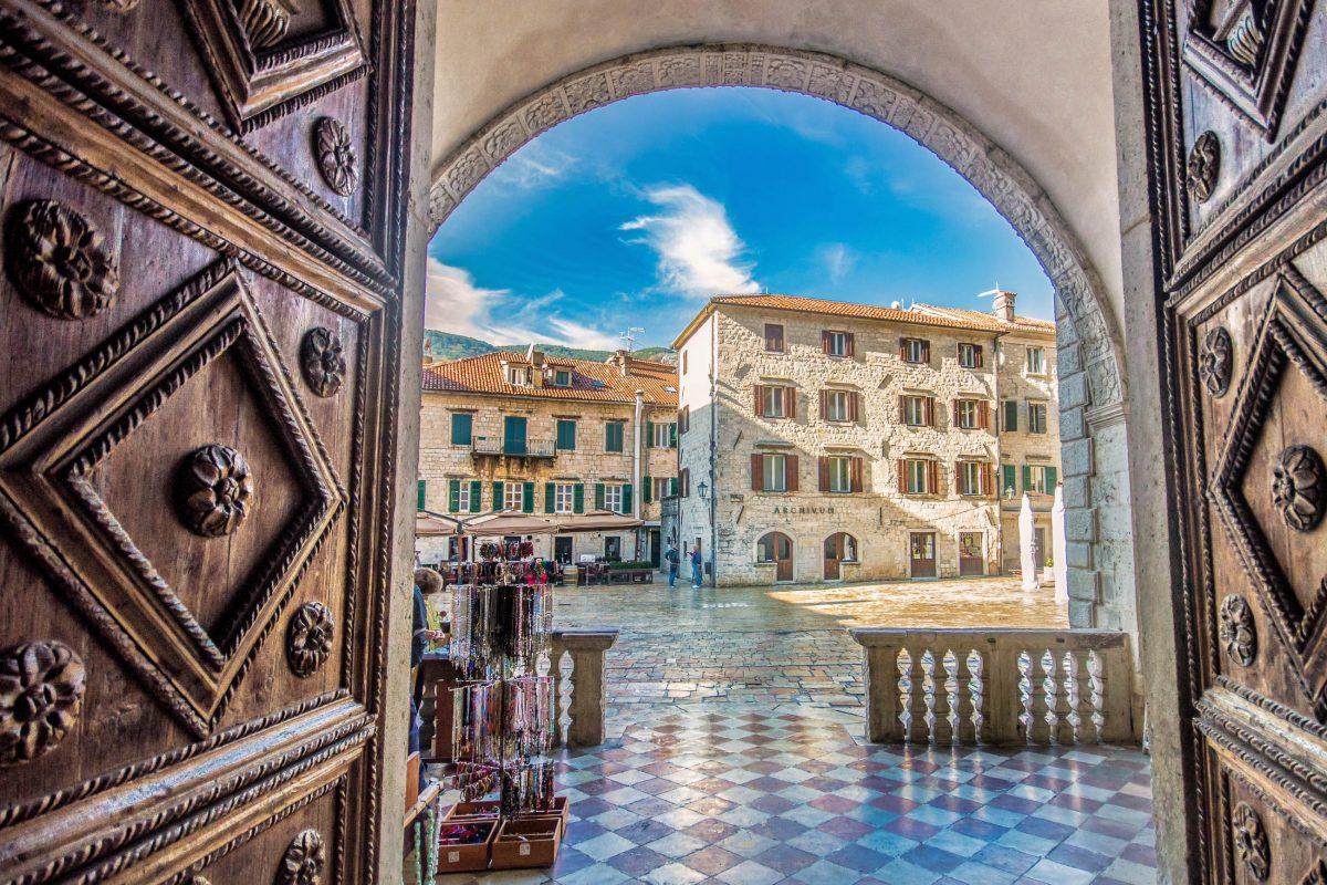 Blick aus der Kirche Sveti Trifun auf den malerischen Trg Ustanka mornara in der Altstadt von Kotor, Montenegro - © Ranko Maras / Shutterstock