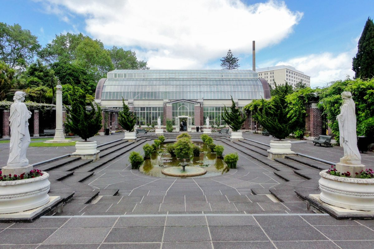 """Die beiden Glashäuser des """"Winter Garden"""" im Auckland Domain flankieren einen hübschen Platz mit Teich und mehreren Statuen, Neuseeland - © Andy king50 CC BY-SA3.0/Wiki"""