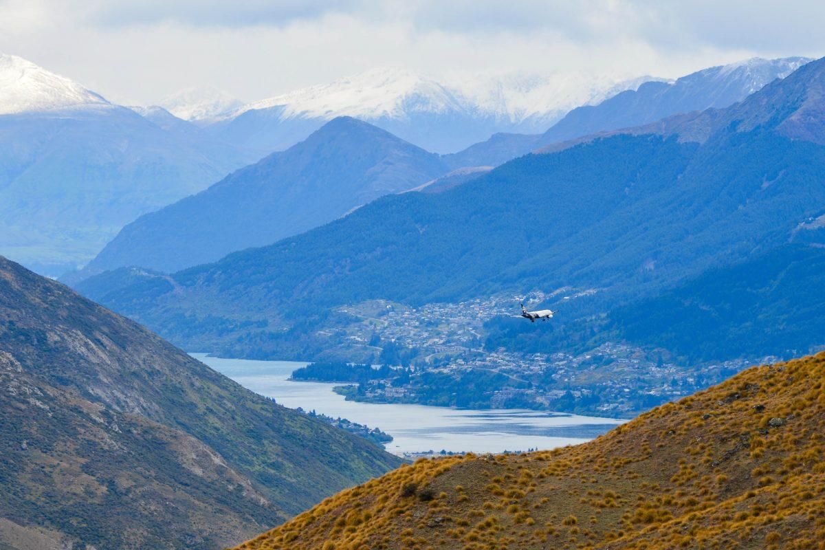 Blick von der Crown Range Road auf ein Flugzeug im Anflug auf Queenstown, Neuseeland - © FRASHO / franks-travelbox