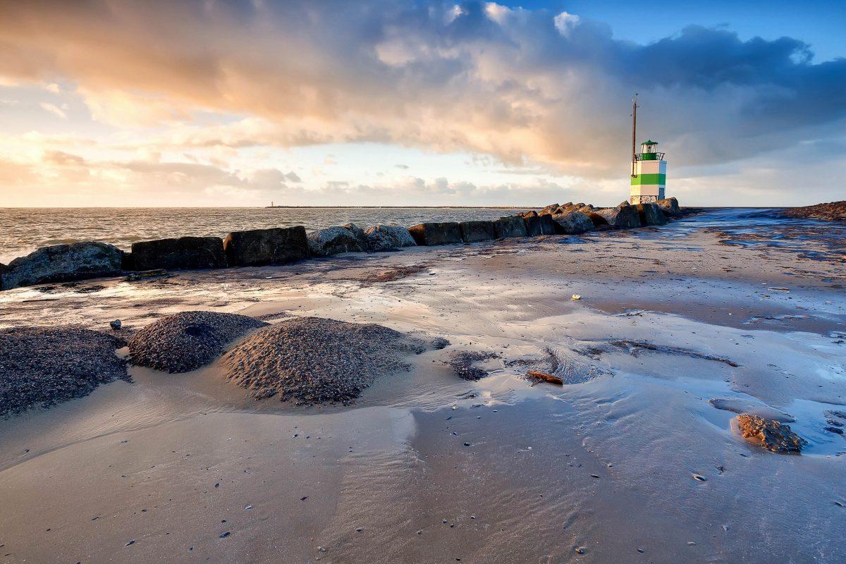 Der Leuchtturm an der niederländischen Nordseeküste in Ijmuiden wird von der untergehenden Sonne in romantisches Licht getaucht - © catolla / Shutterstock