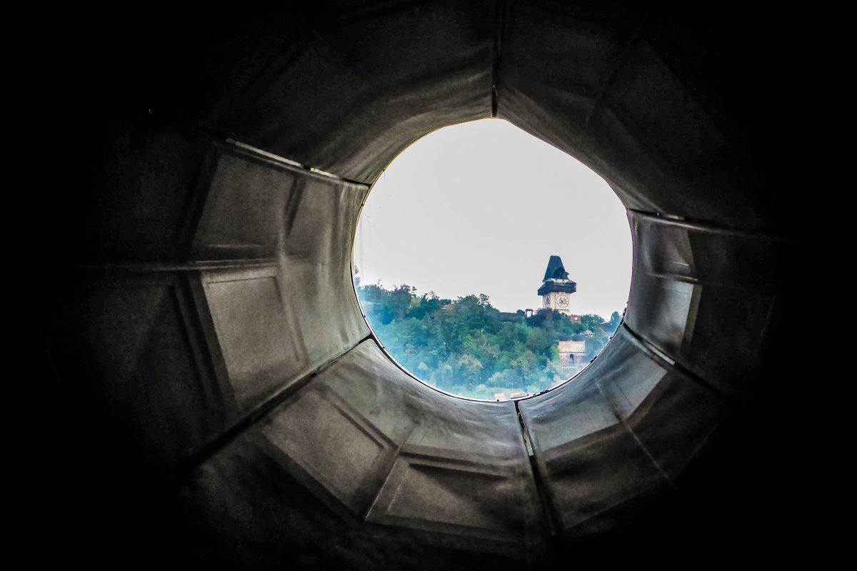 """Durch einen nach Osten gerichteten Nozzle (""""Düse"""") fällt der Blick im Kunsthaus direkt auf den berühmten Grazer Uhrturm, der quasi so ebenfalls als """"Exponat"""" zu sehen ist, Österreich - © Lila Pharao / franks-travelbox"""