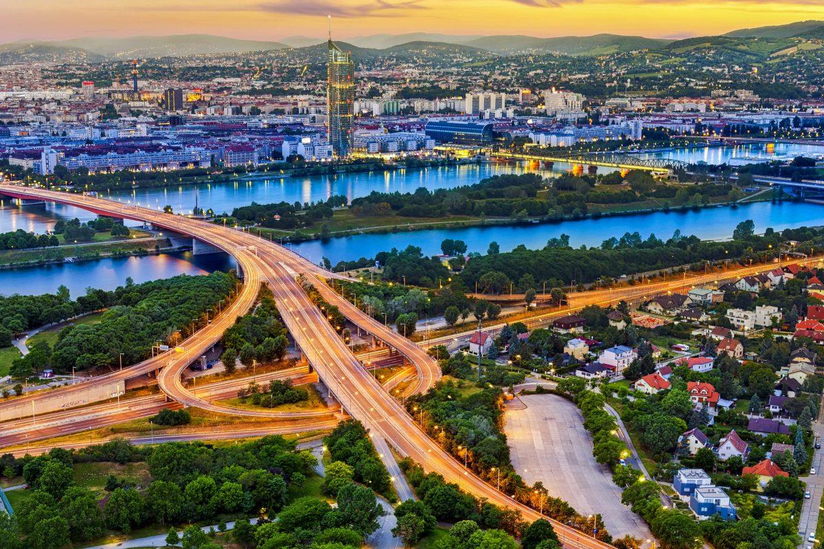 Blick auf die Donau und die Donauinsel als Kulisse für die beleuchtete Autobahn A22 in der Dämmerung in Wien, Österreich - © Creativemarc / Shutterstock