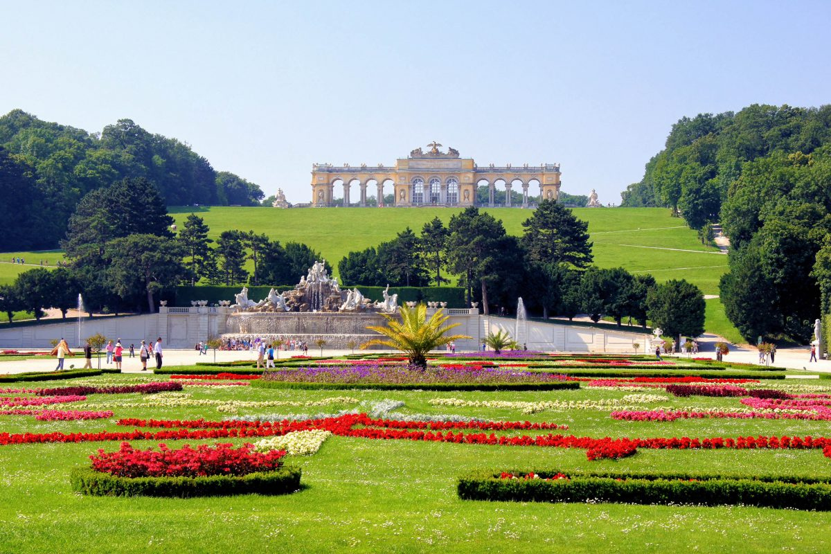 Die Blumenarrangements des herrlichen Schönbrunner Schlossparks erstrecken sich bis zum Neptunbrunnen am Fuß des Hügels mit der Gloriette, Wien, Österreich - © JeniFoto / Shutterstock