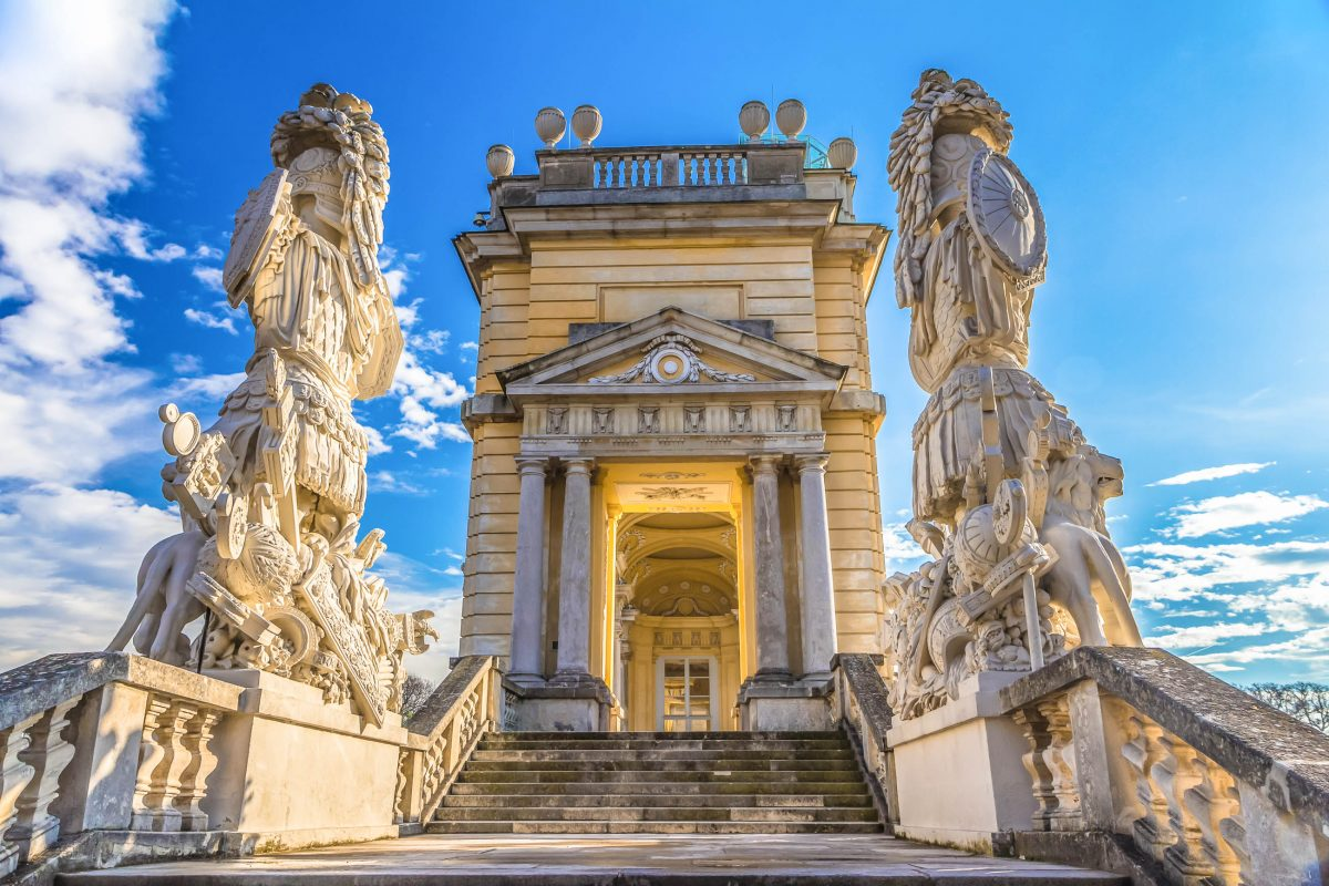 Die seitlichen Treppenanlagen der Gloriette in Wien werden von mächtigen Figuren gesäumt, die Rüstungen, Adler, Löwen und Feldzeichen darstellen, Österreich - © pavel068 / Shutterstock