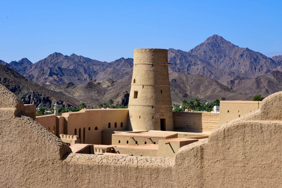 Die hellen, sandfarbenen Mauern der Festung von Bahla heben sich deutlich vor dem dunklen Hintergrund des gewaltigen Gebirgszuges Jebel Akhdar ab, Oman - © FRASHO / franks-travelbox