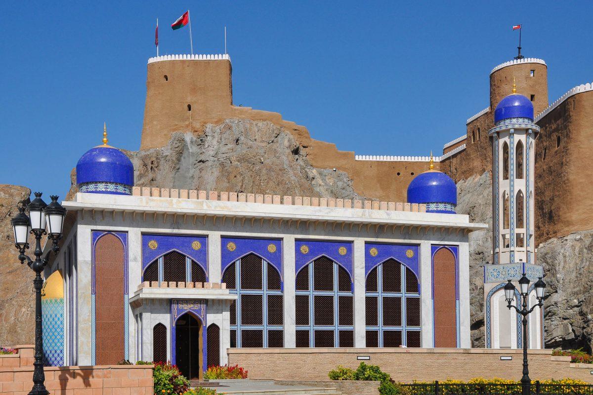 Blaue Kuppeln und blaue Kacheln dominieren die Fassade der Al Khor Moschee von Muscat, die in starkem Kontrast zum graubraunen Fort Mirani dahinter stehen, Oman - © Claudiovidri / Shutterstock