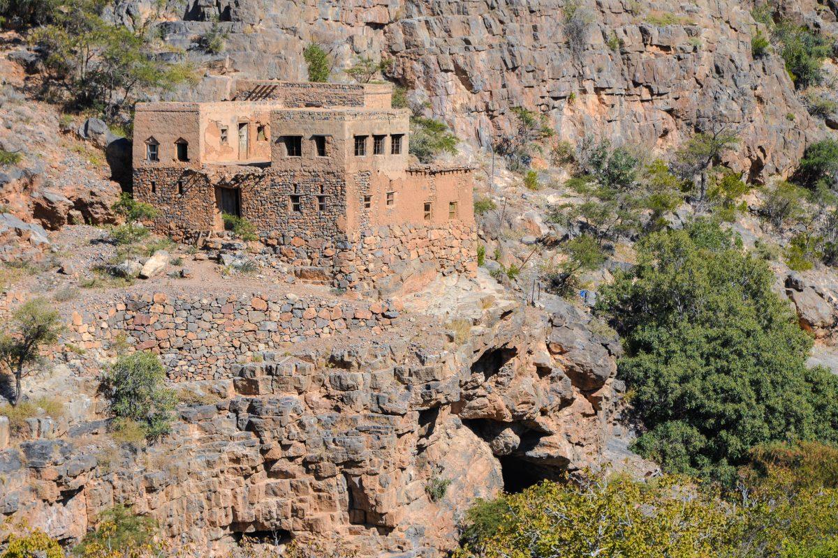 Die teilweise verwitterterten Lehmhütten im Wadi bani Habib schmiegen sich wie Spielzeughäuschen an die steile Flanke des Berges, Oman - © FRASHO / franks-travelbox