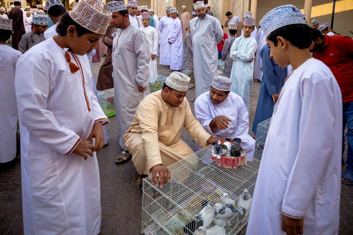 Junge Burschen stehen am Tiermarkt von Nizwa um die Männer herum um zu lernen und bald selbst in die Geschäfte einsteigen zu können, Oman - © clicksahead / Shutterstock
